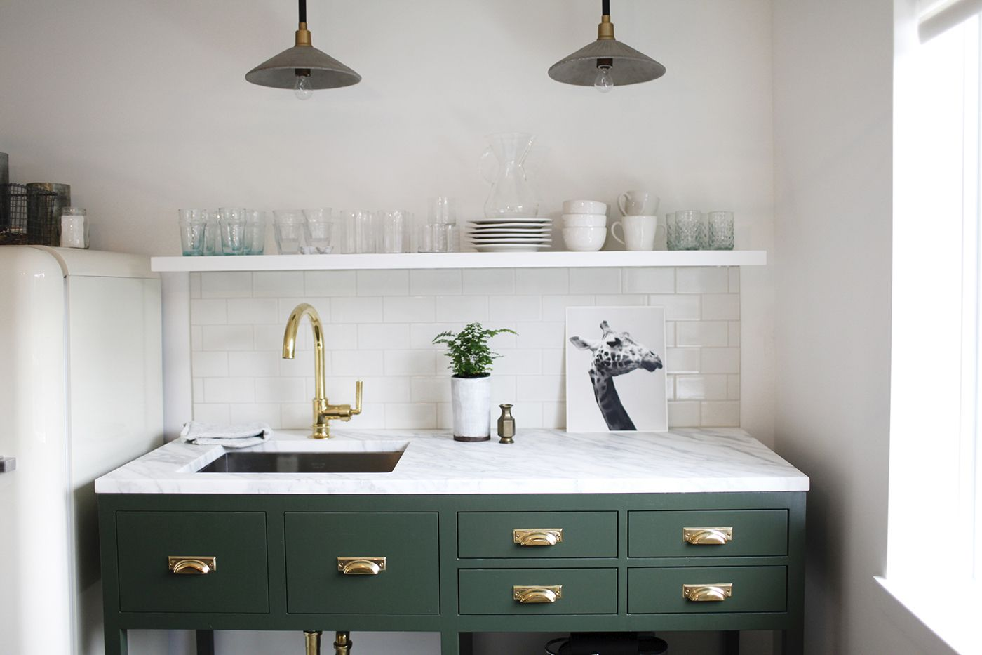 A light-filled kitchen with green cabinets
