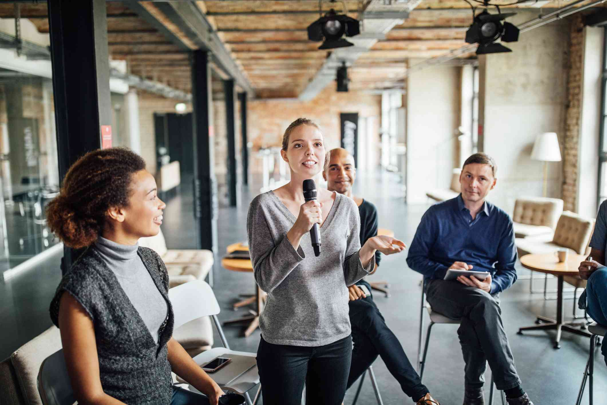 Woman speaks into microphone, coworkers watch