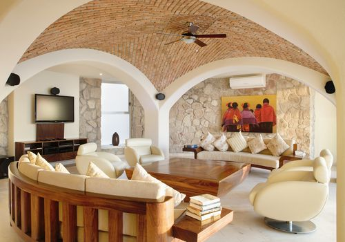 A midcentury-modern living room in a Spanish villa with a tan, bricked vaulted ceiling, beige modern furniture, stone walls, and wood accents