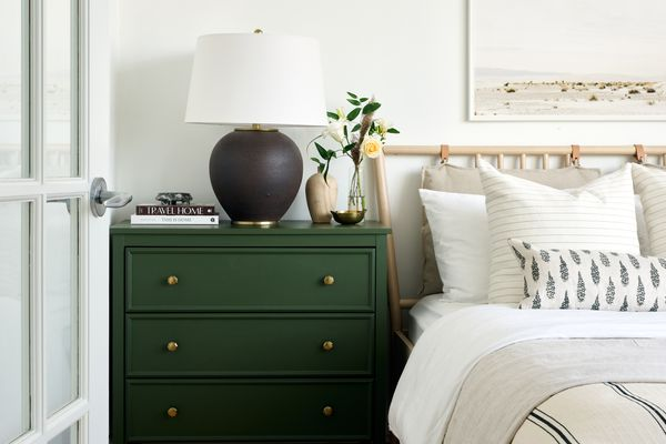 Neutral bedroom with forest green nightstand and black lamp.