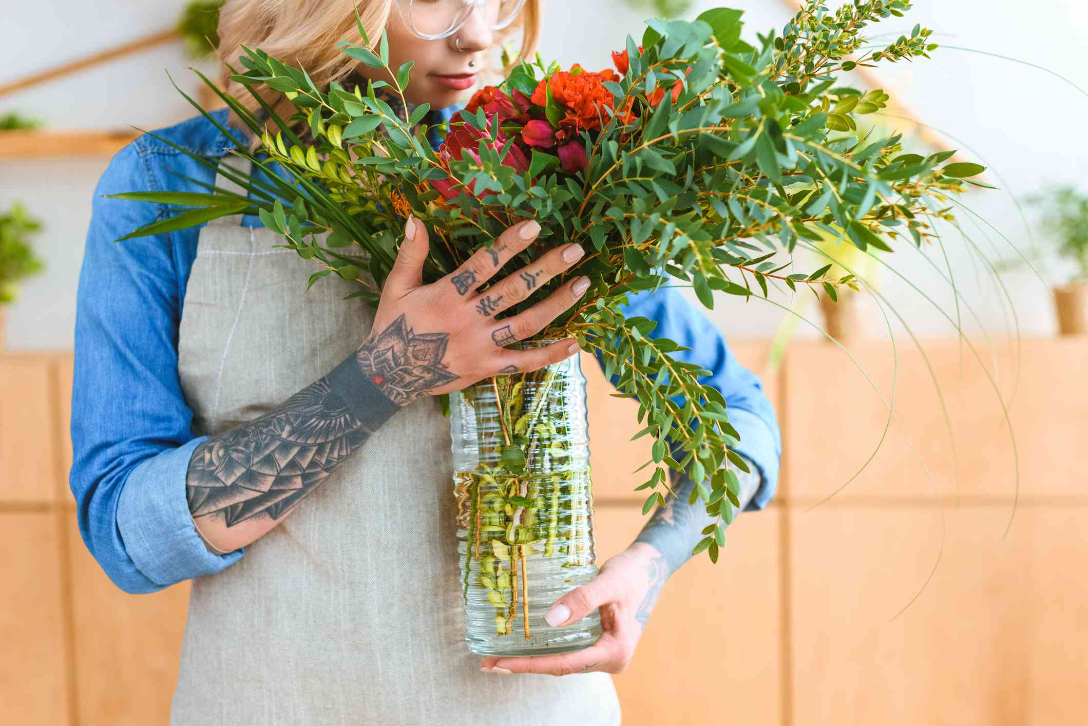 tattooed woman holding a vase of cut flowers