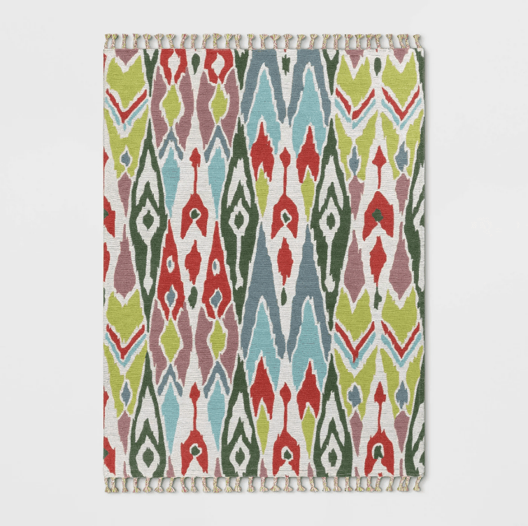 A multicolored rectangular ikat rug with fringed edges.