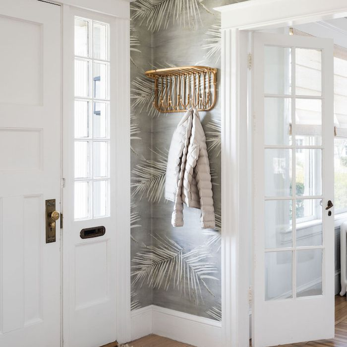 entryway with gray frond wallpaper and golden decorative hanging coat rack/shelf