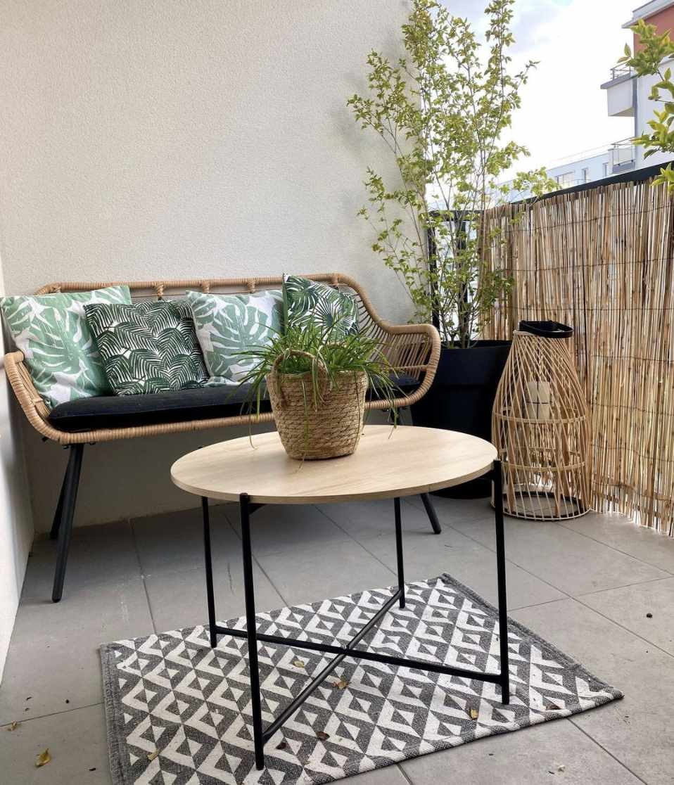 balcony with simple wicker bench, green pillows, wooden round table on top of gray and white pattern rug