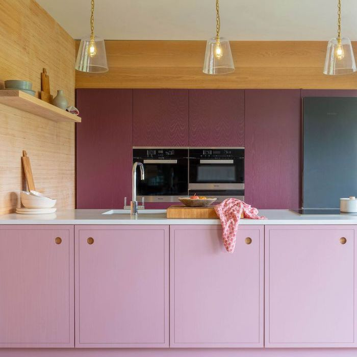 light pink and plum cabinets with wooden wall