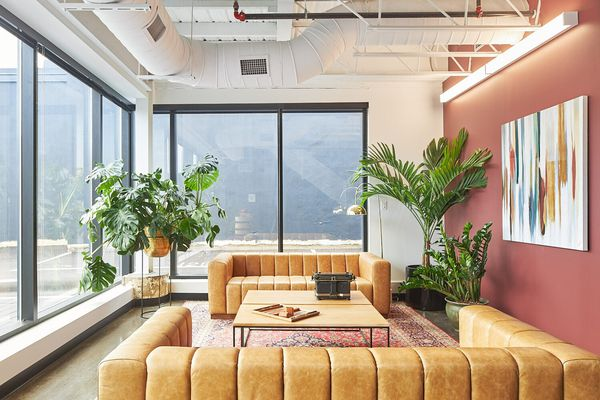Magenta painted office with caramel colored couches.