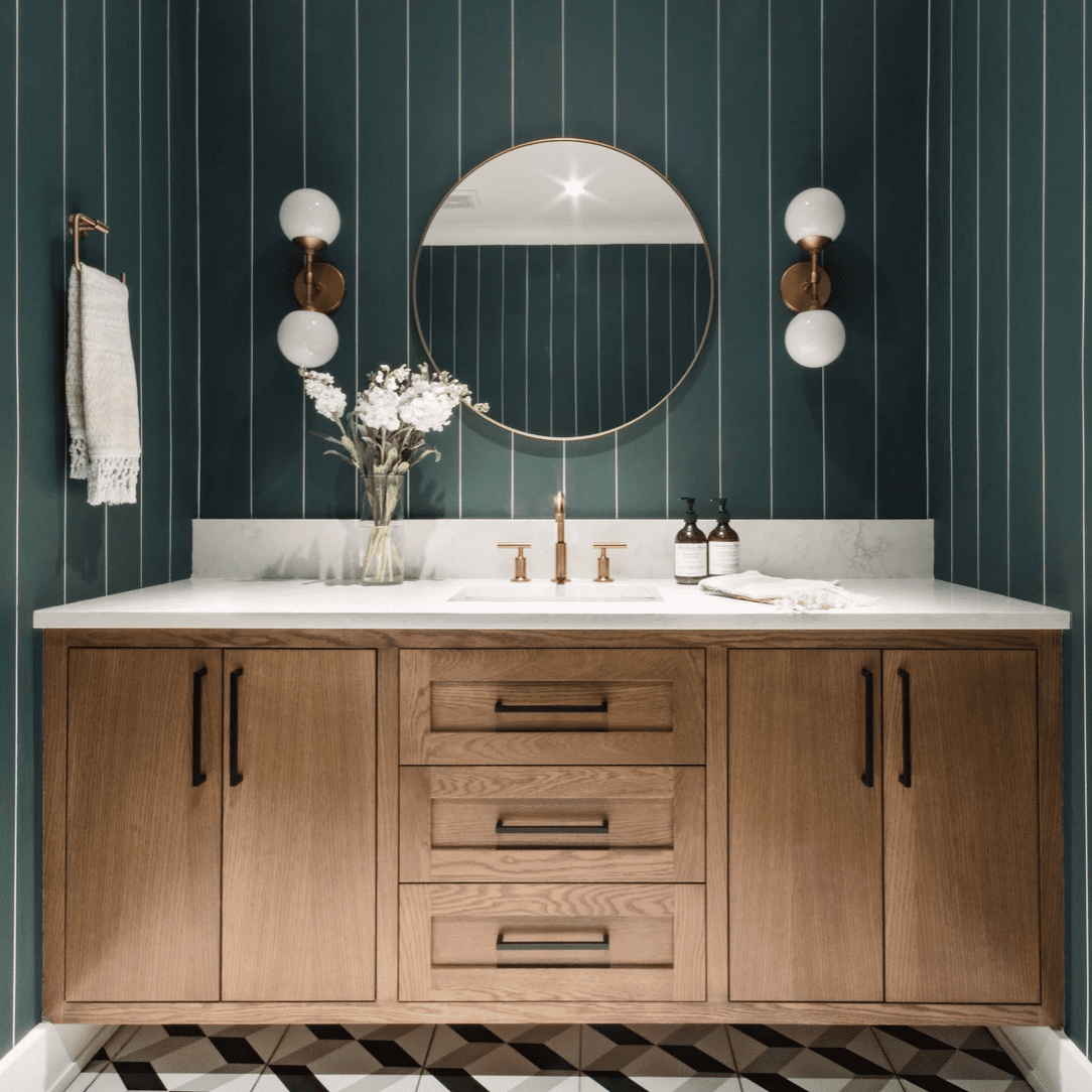 A large powder room with dark green wallpaper