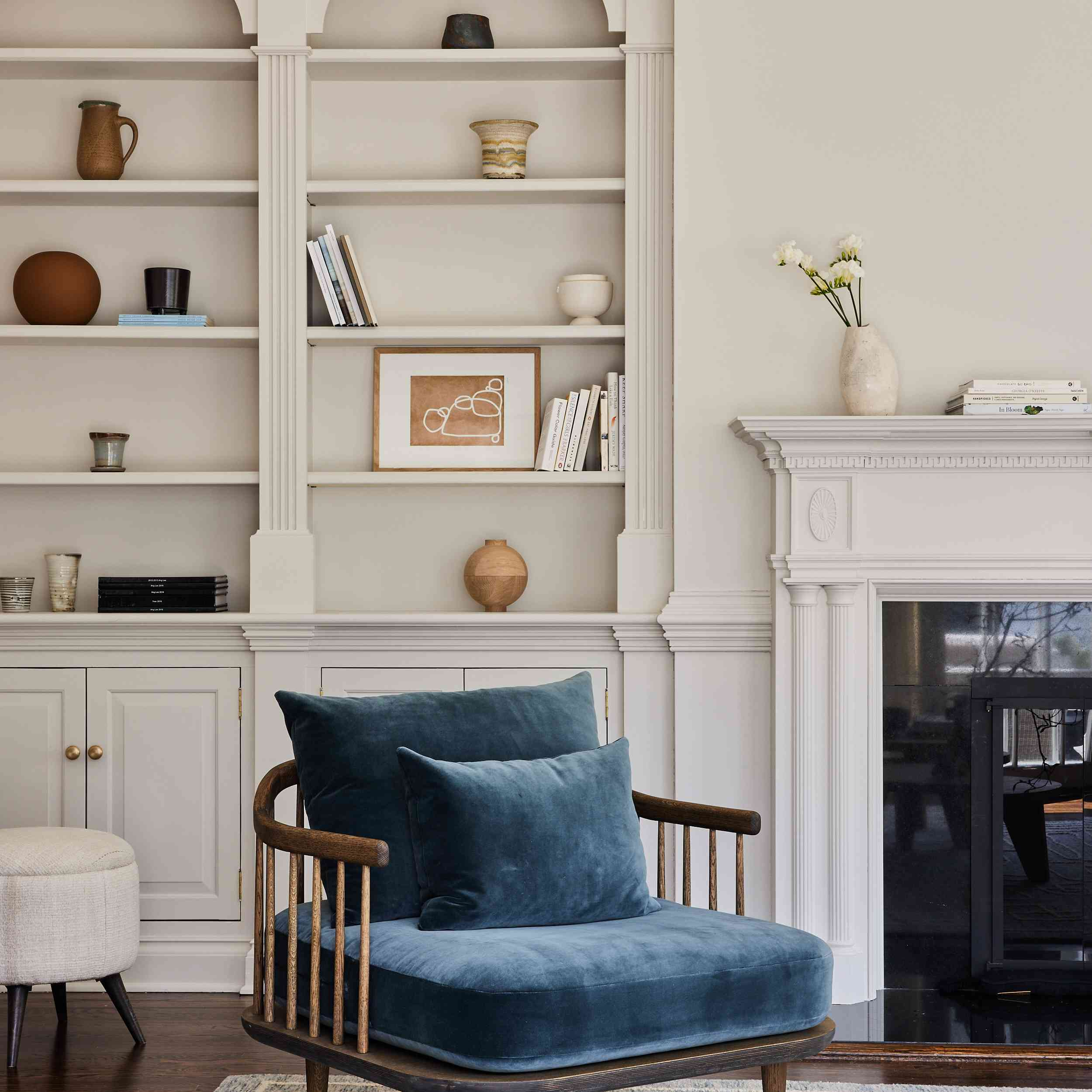 connecticut farmhouse home tour - blue velvet accent chair in front of arched built-in bookcases