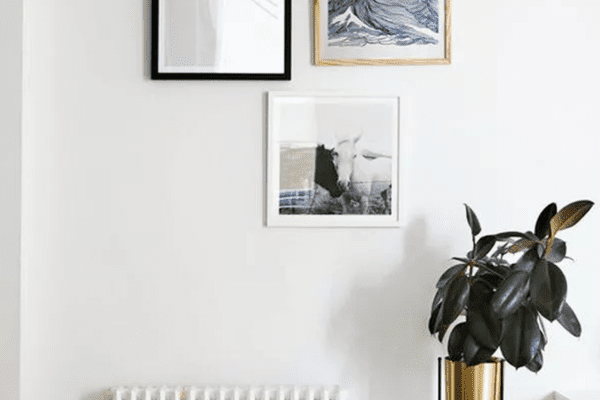 Plant stand positioned beneath framed wall art