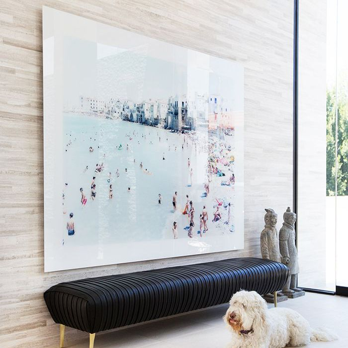 Entryway features large-scale photograph, seating, and a dog perched next to it