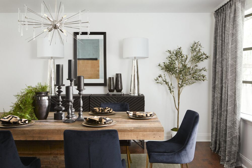 Muted glam dining room with wood table and blue velvet chairs