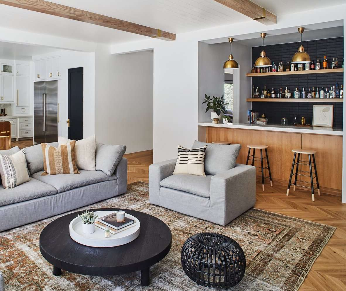 A living room flanked by a bar and an open-concept kitchen