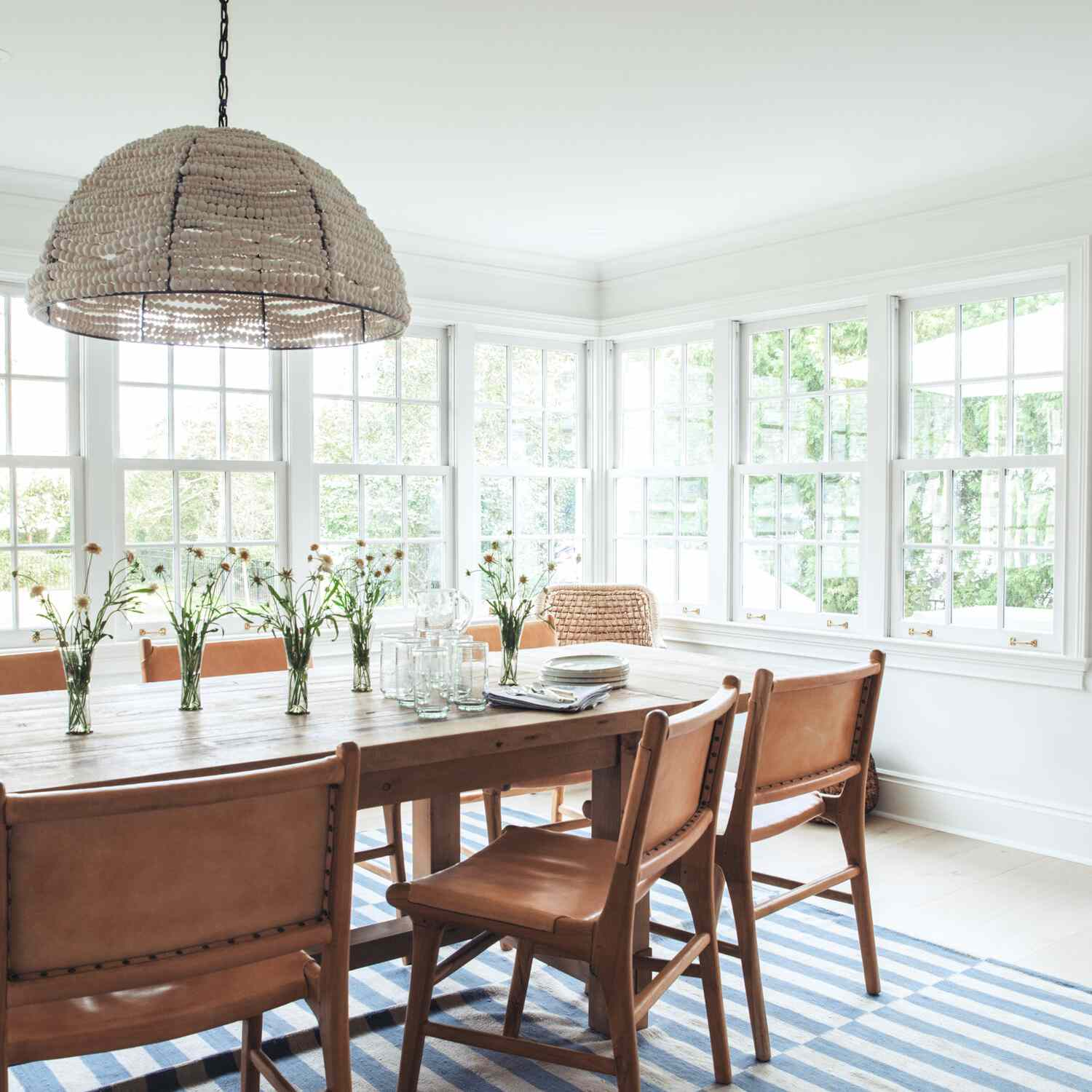 A dining room with sleek wooden furniture and a graphic blue and gray striped rug