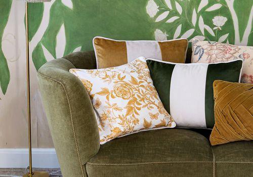 Sézane lanza su primera colección para el hogar: sofá verde con almohadas