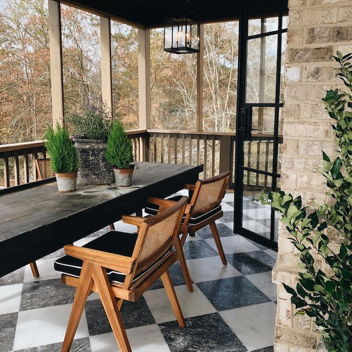 Screened in porch with checkered tile flooring and table.
