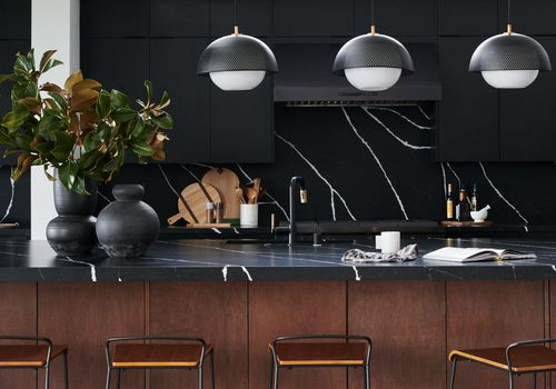 all-black kitchen counter and wall with wood accents
