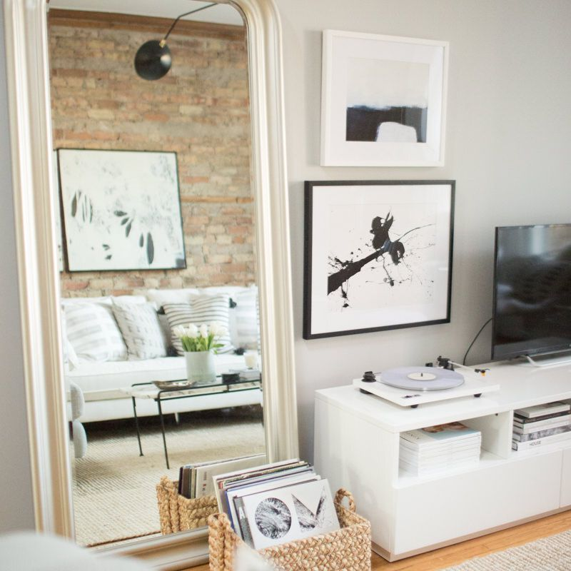 Large leaning mirror in white Scandi living room.