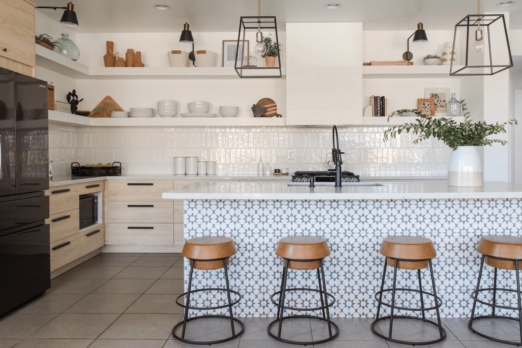 A kitchen with a backsplash lined with white tiles and a kitchen island lined with printed tiles