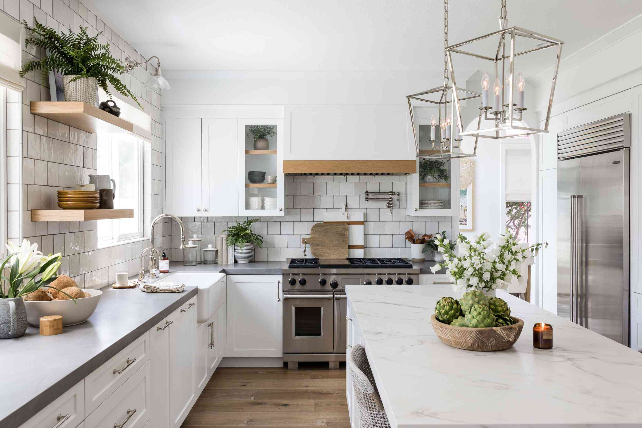 A white kitchen with a backsplash made from white tiles and dark grout