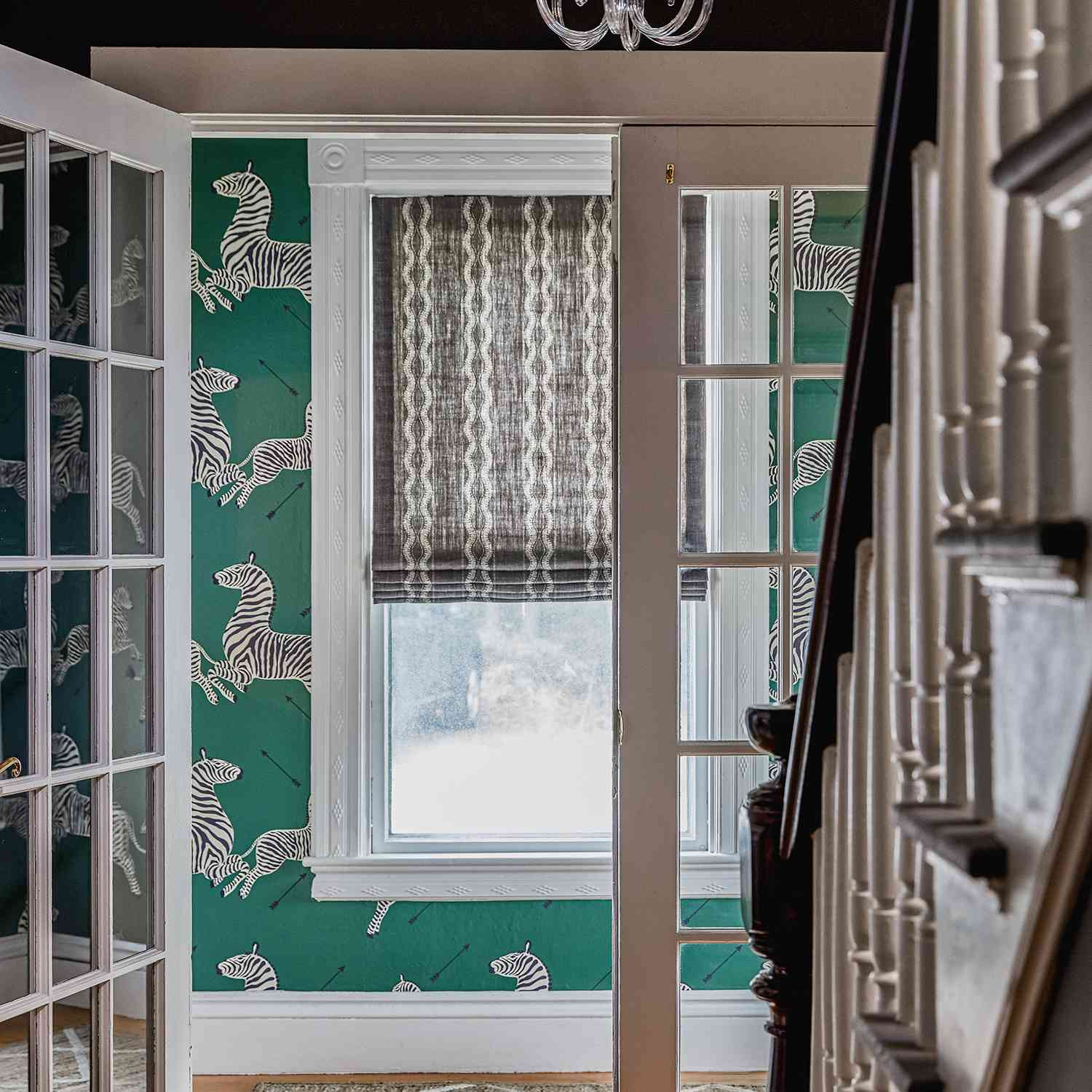 A hallway lined with green zebra print wallpaper