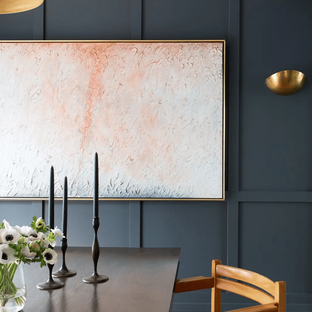 A dining room with an indigo wall topped with a light pink painting