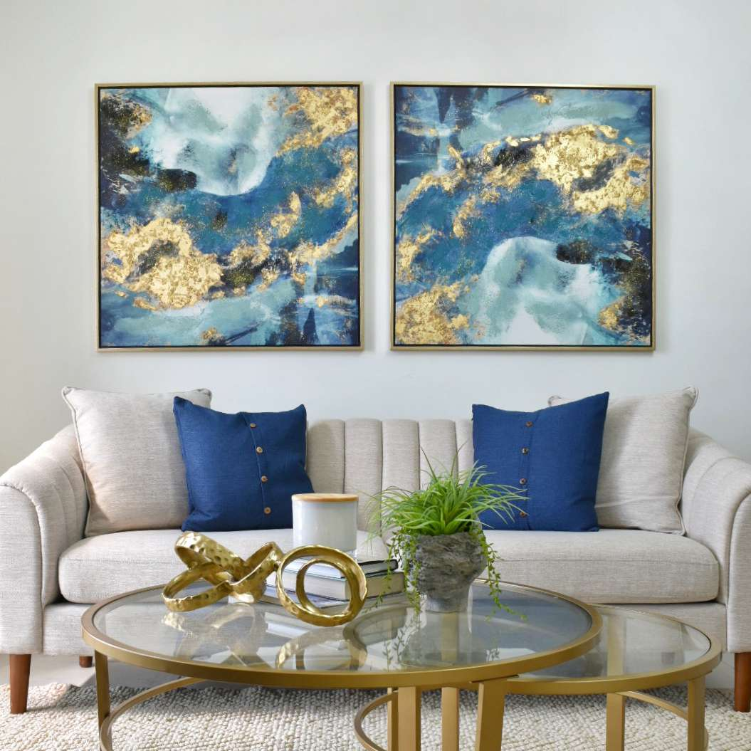 Neutral sofa with blue and gold marbled artwork above.