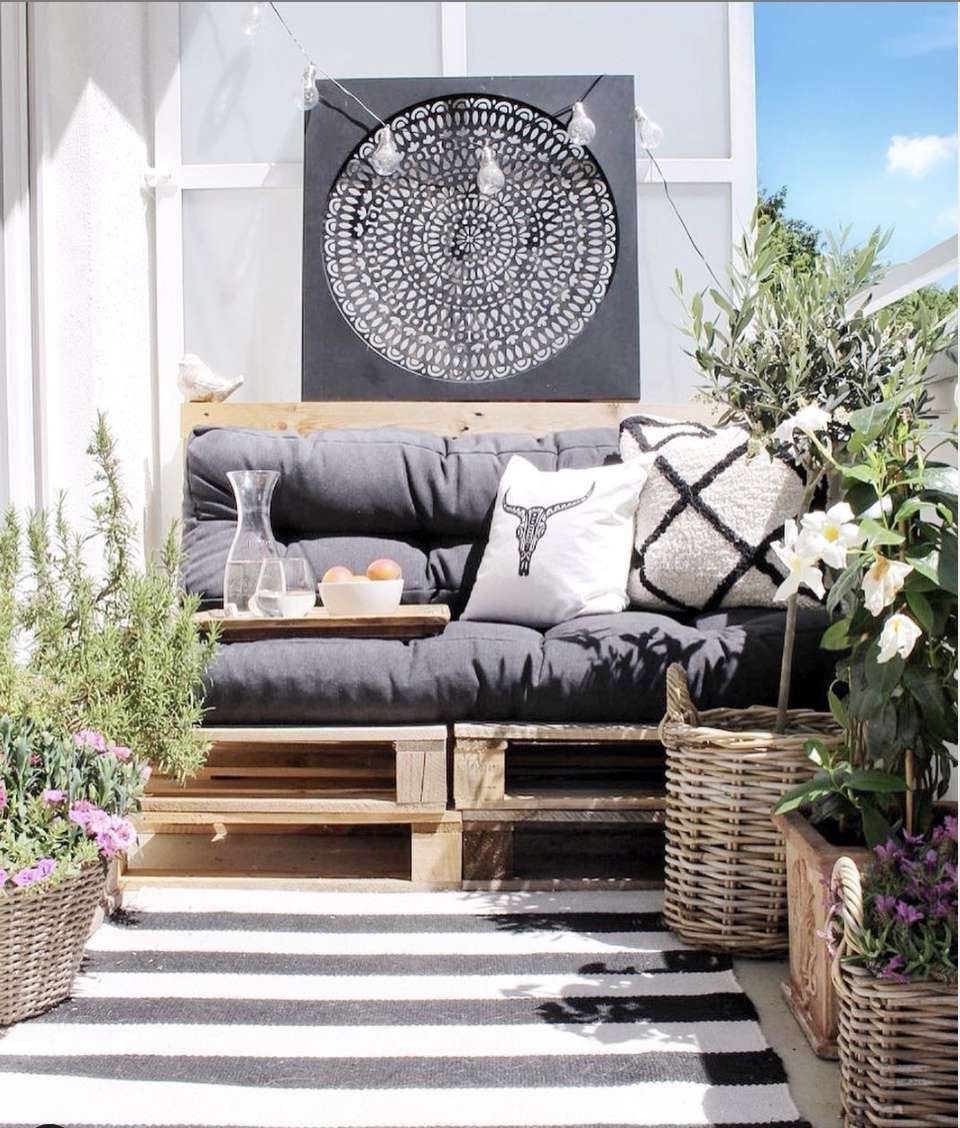 balcony with wood pallets and black cushions as eating,