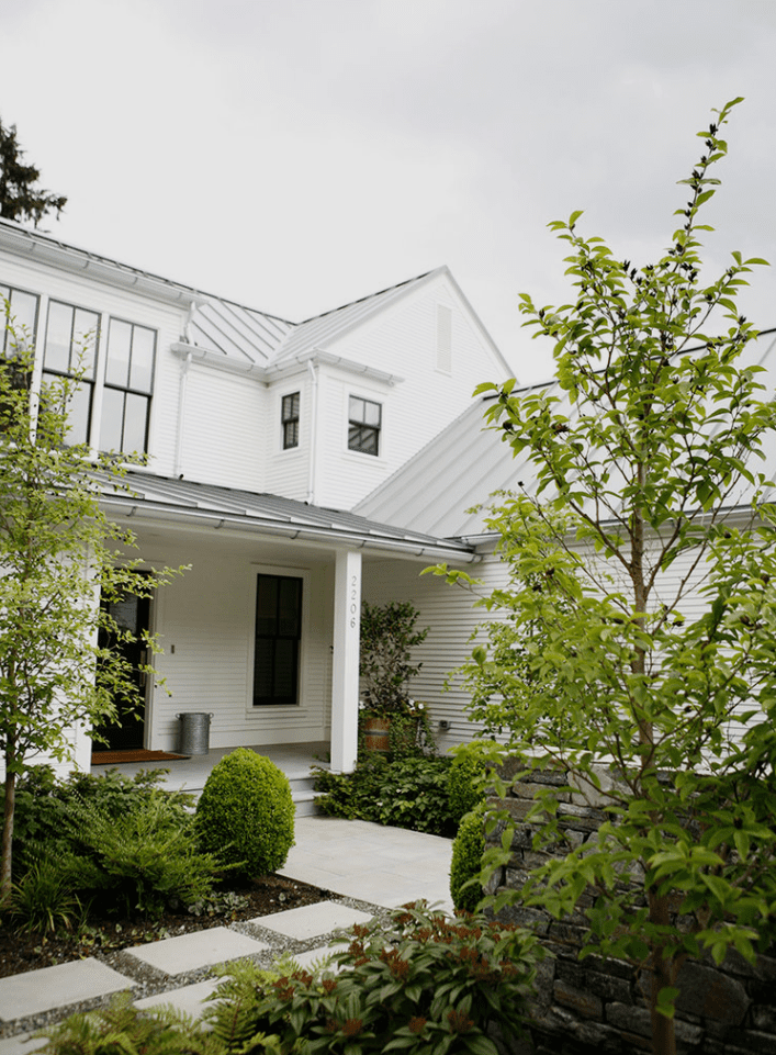 Modern farmhouse exterior with lots of greenery.