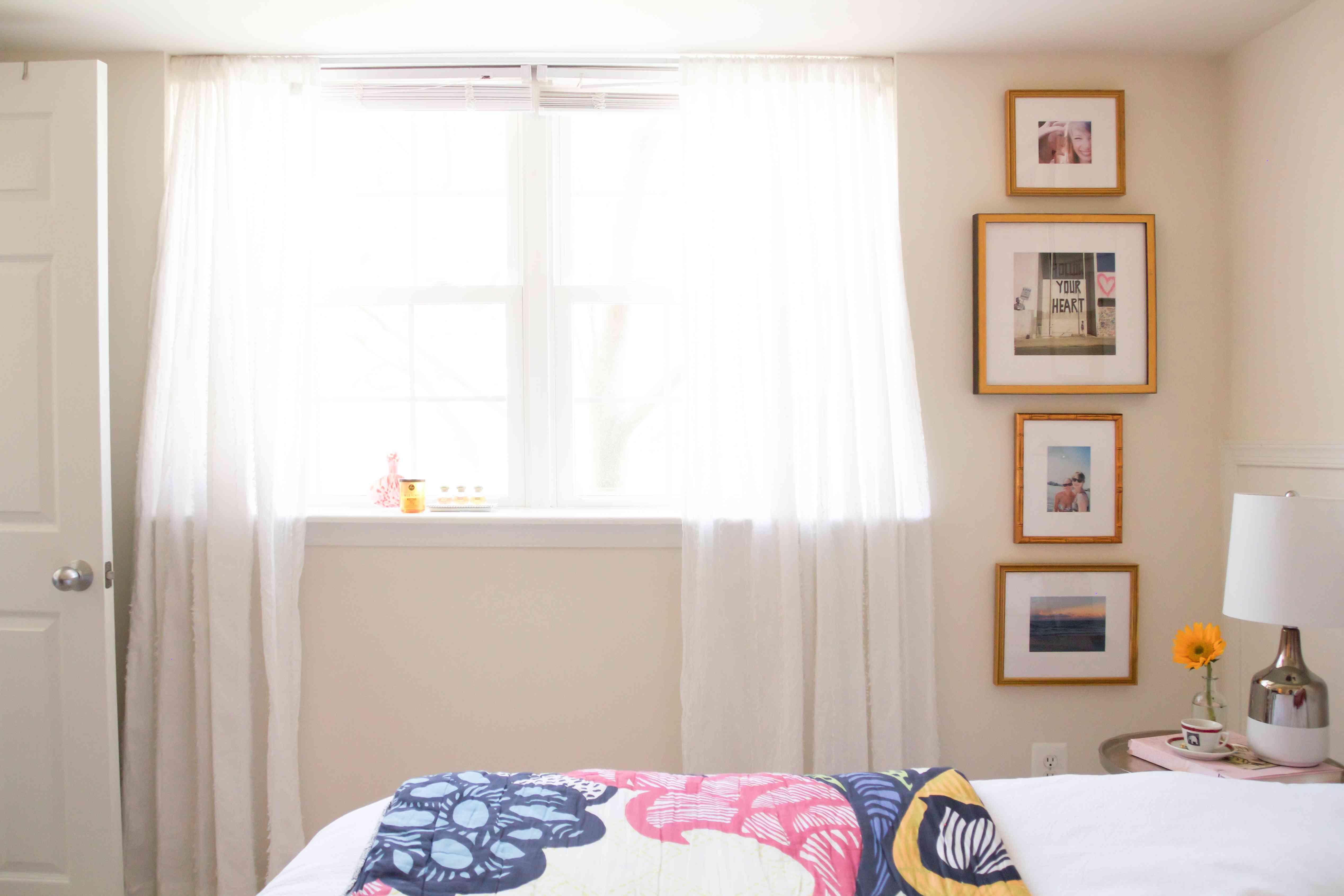 Framed photos in vertical lineup beside a window in bedroom.