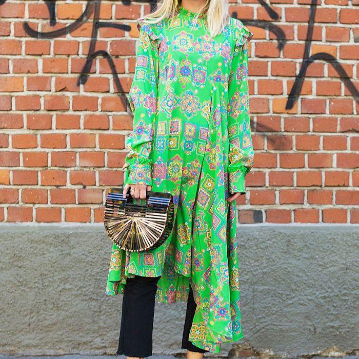 una mujer con un vestido midi, jeans negros y tacones