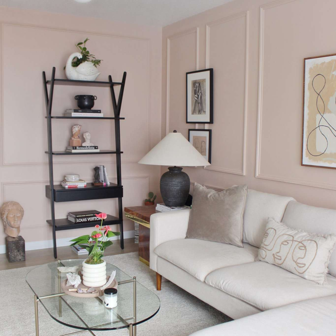 Modern pink living room with tiered bookshelf.