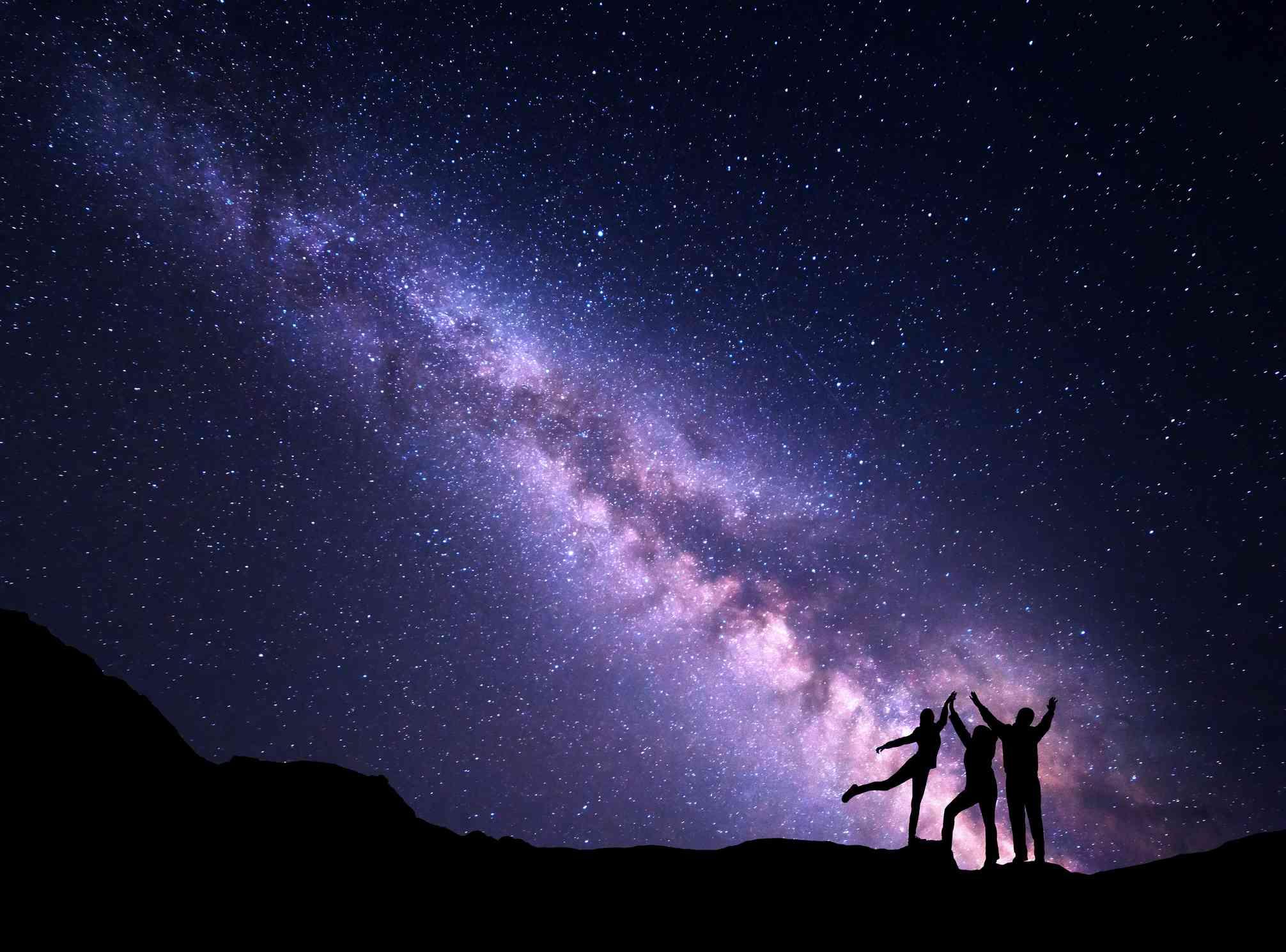 Silhouette of three friends stargazing