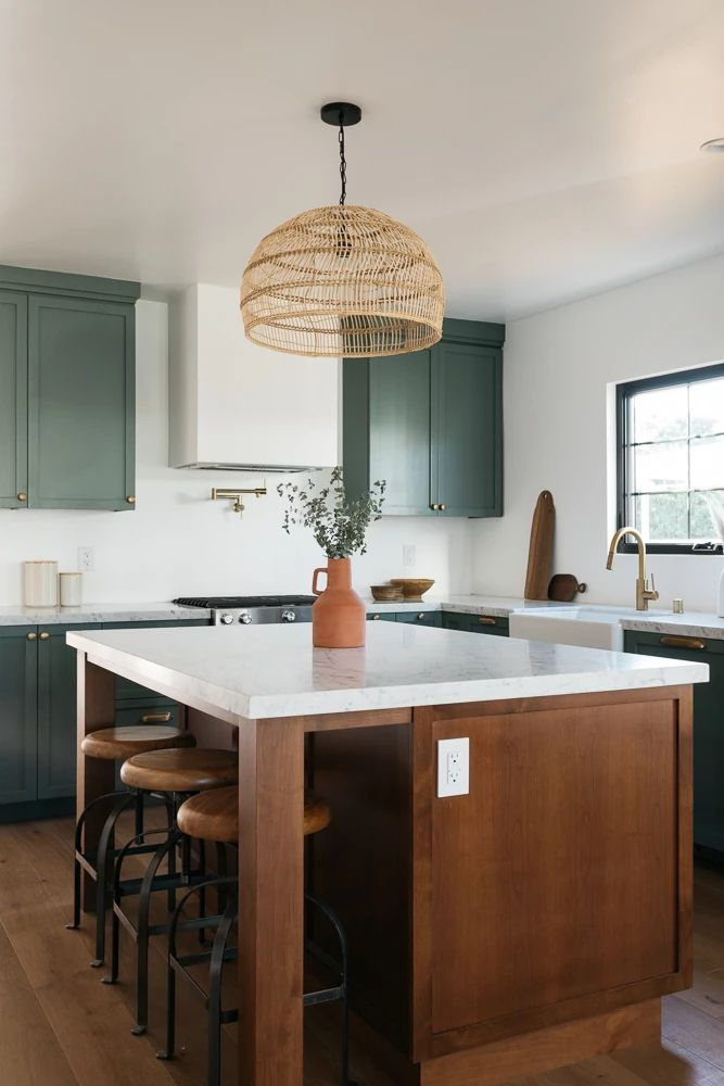 Kitchen with green cabinets and wood island.