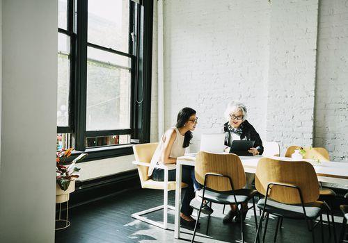 Dos mujeres se sientan juntas en la mesa de conferencias, mirando una pantalla de computadora portátil y tableta.