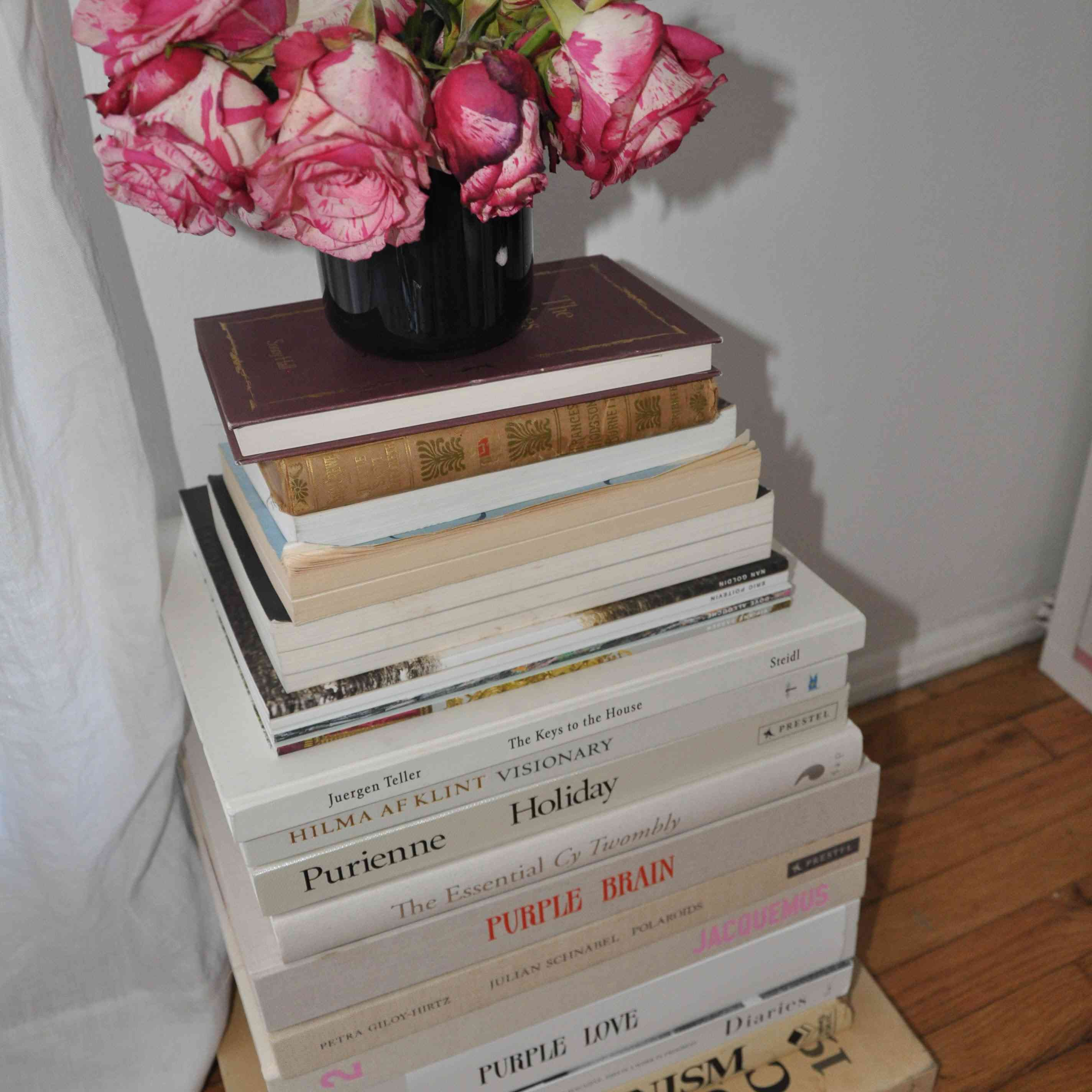 Large stack of books with roses on top.