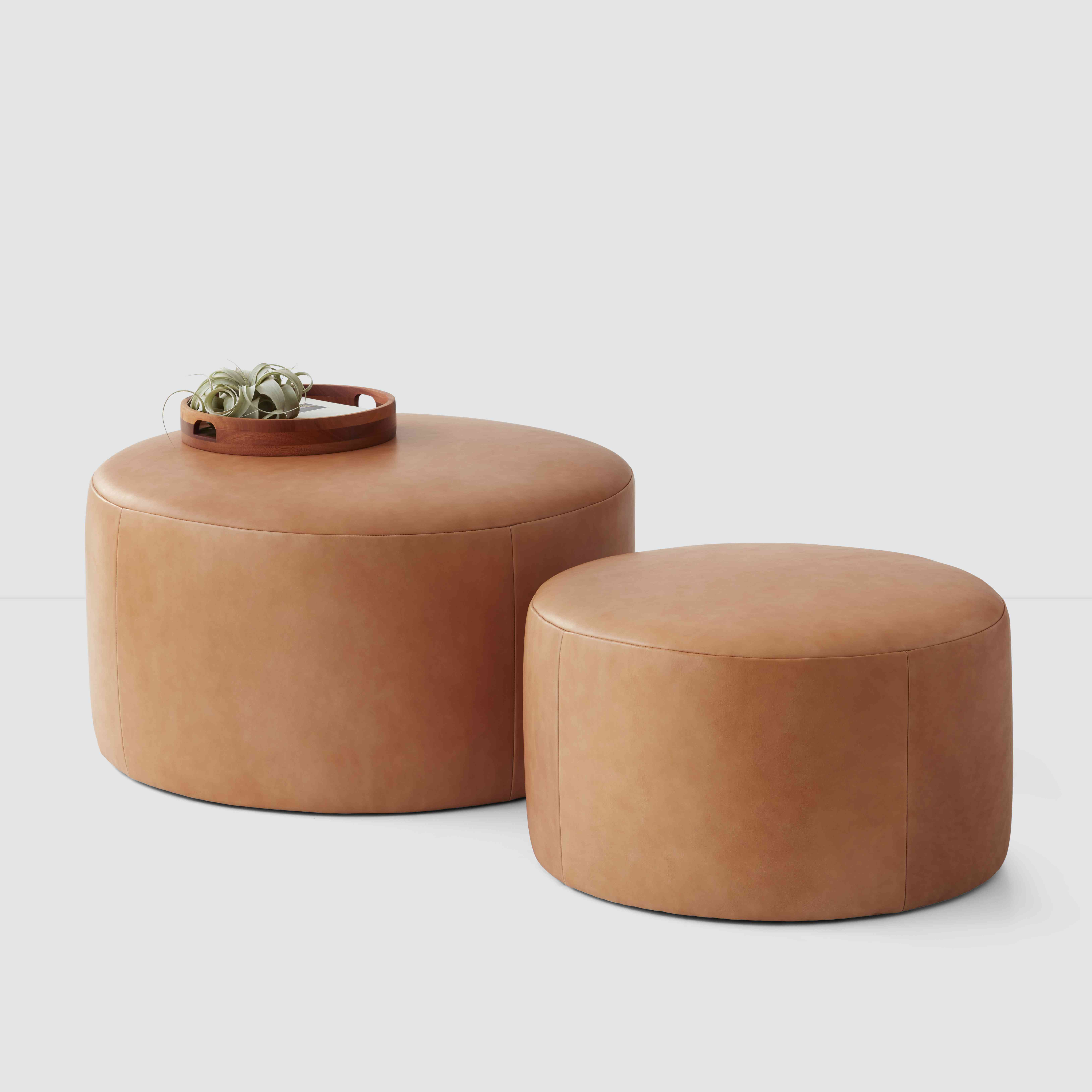pair of caramel colored round leather ottomans