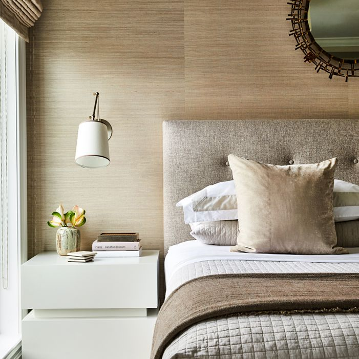 Neutral bedroom with brass mirror.