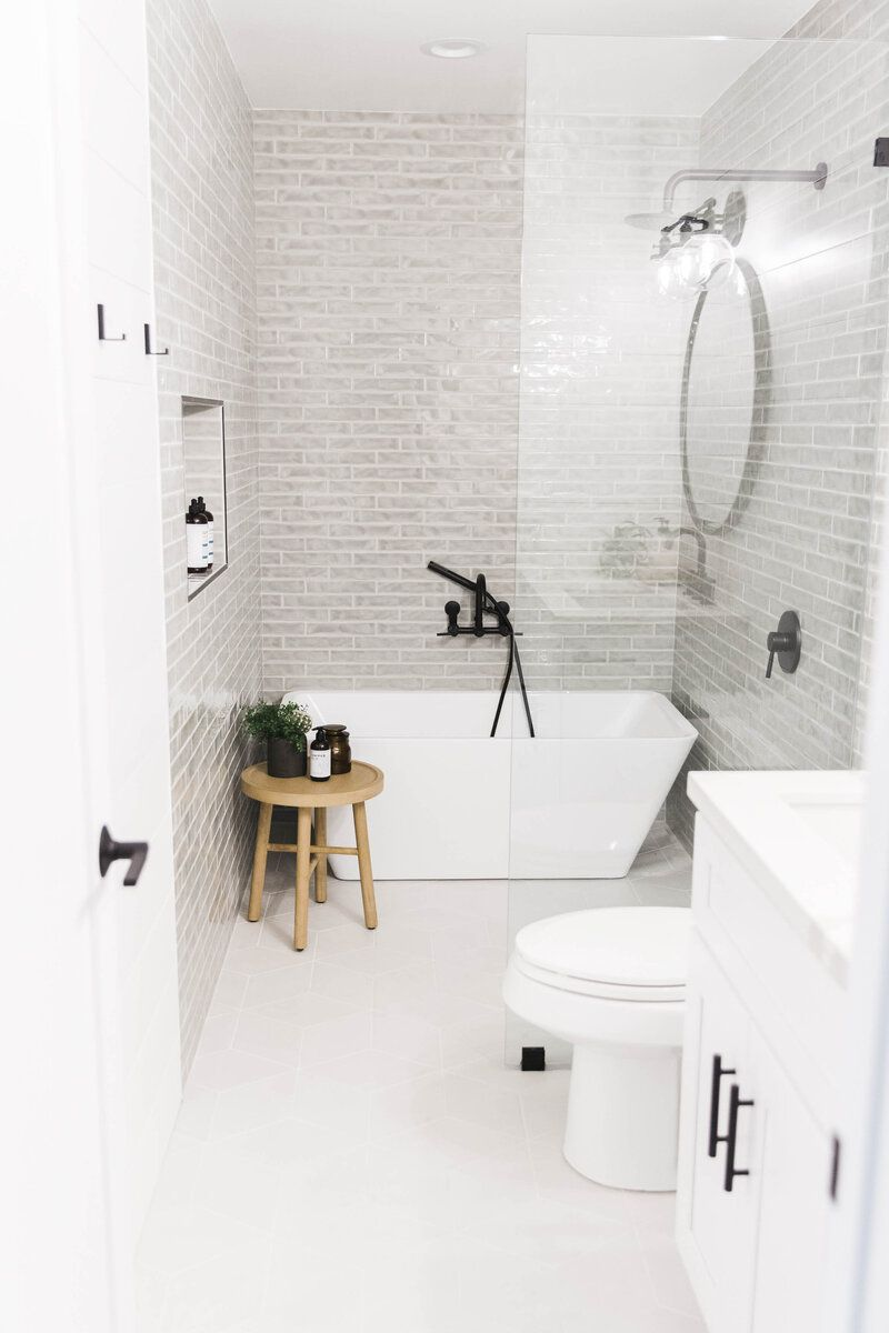 tiled bathroom with freestanding tub, toilet and vanity
