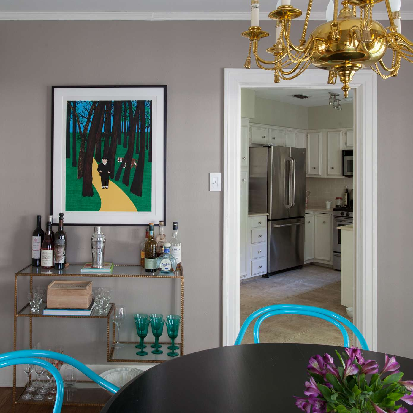 A neutral-filled dining room with vibrant teal accents, including the dining room chair chairbacks and a small graphic print on the wall