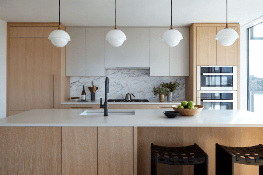 Kitchen with black and white marble and light wooden cabinets.