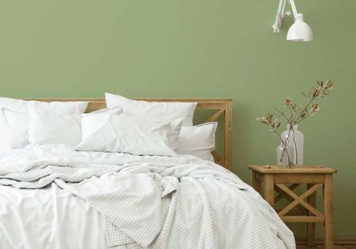 Cozy bedroom with white bedding and Guacamole on wall.