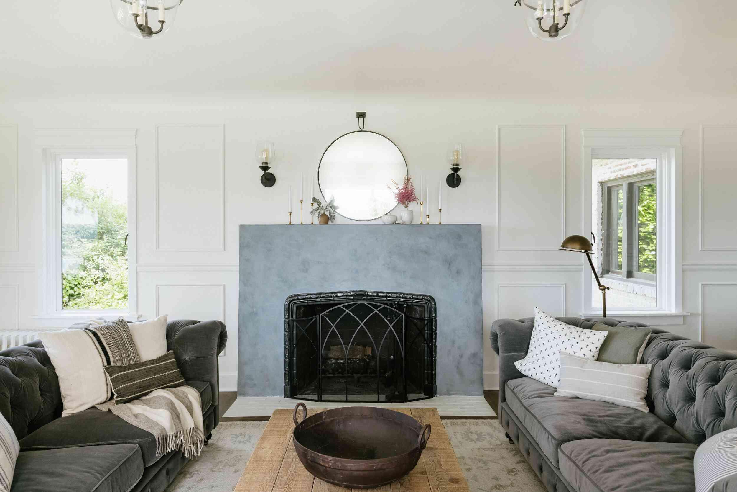 White living room with gray velvet sofas.