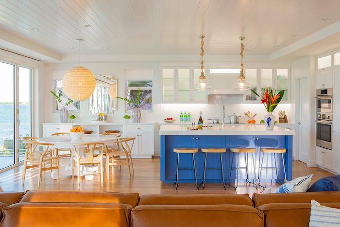 white kitchen accented in wood, bright blue kitchen island