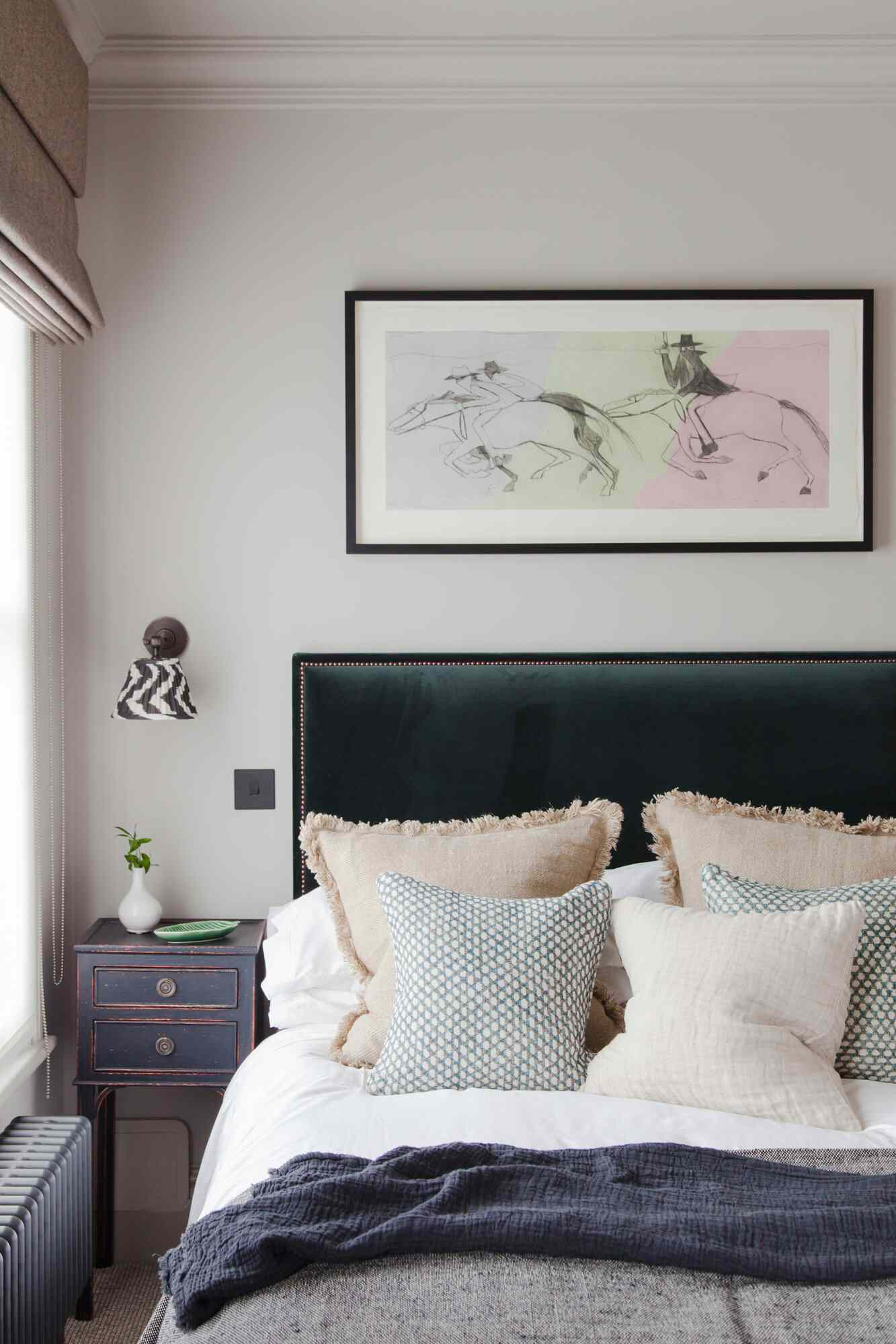 A bedroom with an emerald green upholstered headboard and several pieces of navy decor