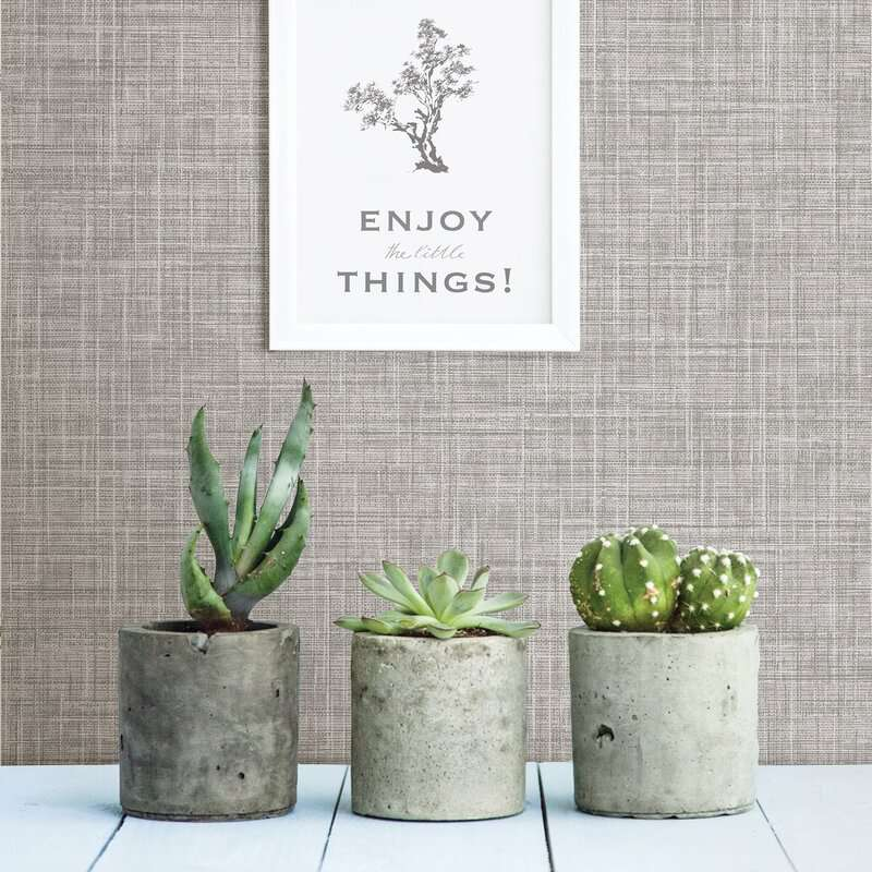 A wall covered in gray fabric wallpaper