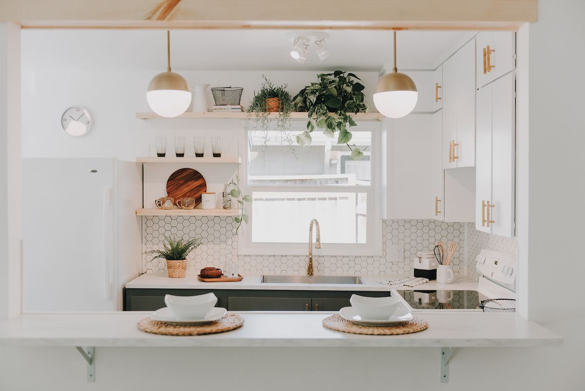 A small white kitchen with statement lighting