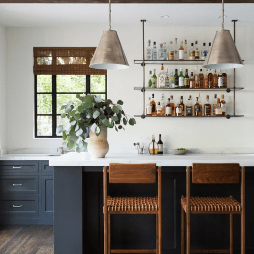A kitchen with a stocked kitchen bar