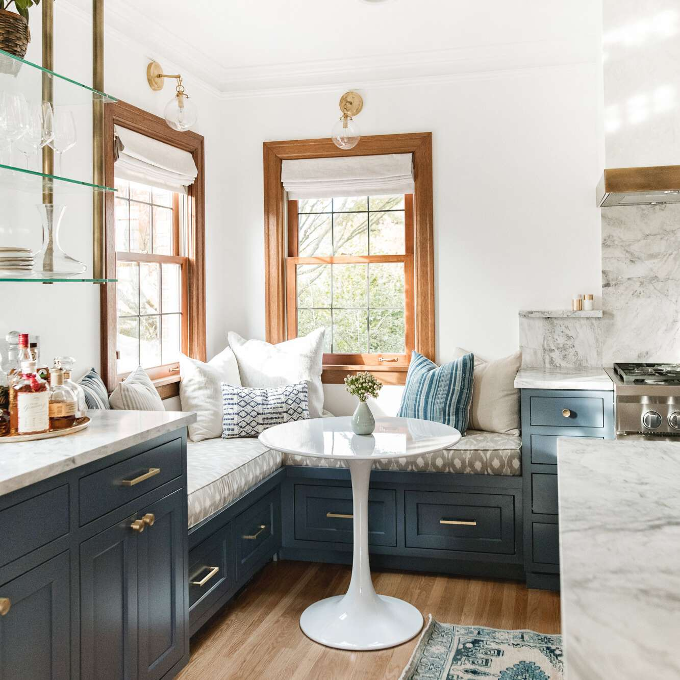 A kitchen banquette built on top of navy cabinets