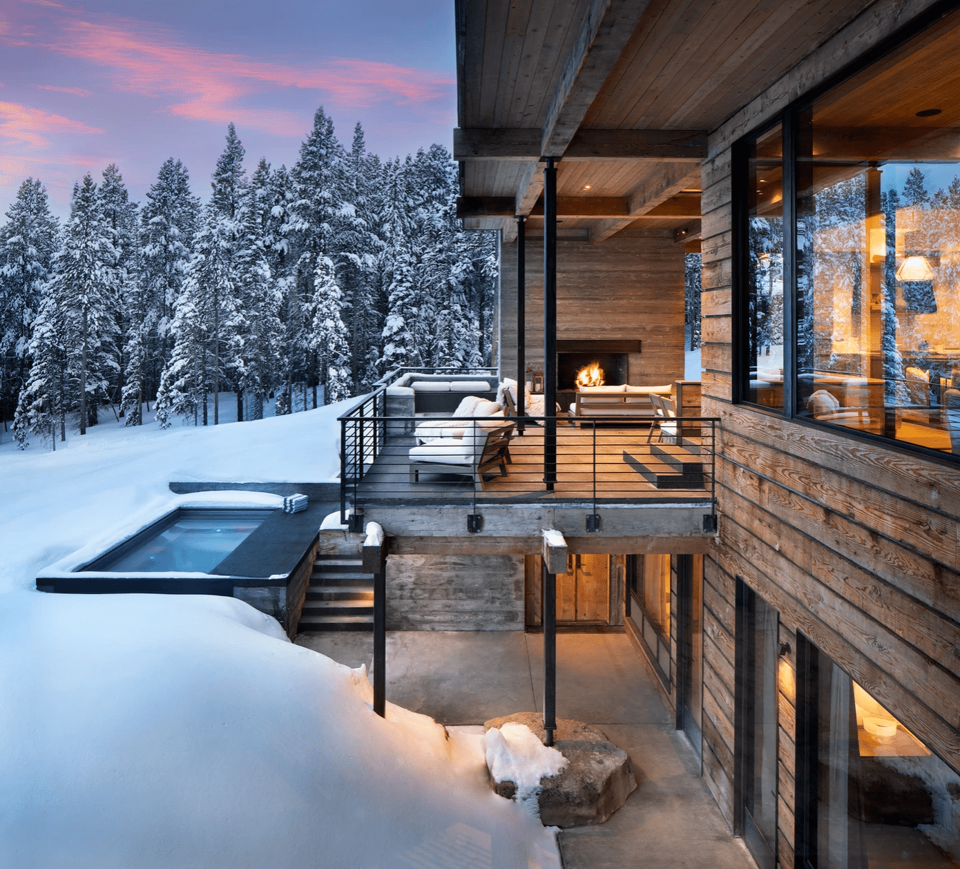 A large covered porch with an outdoor fireplace, situated in the middle of snowy mountains