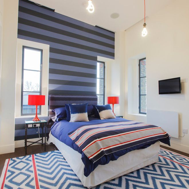 Modern striped-themed bedroom with blue and black striped accent wall.